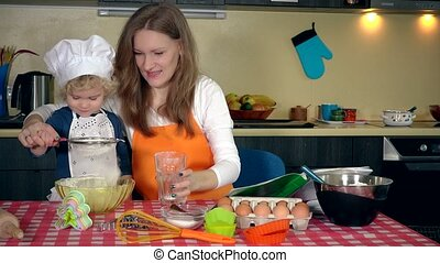 Loving mother with her excited cute daughter girl sifting flour in kitchen