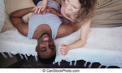 Loving multiracial couple lying on the bed in pajamas. Man and woman hugs, spending morning together at home.