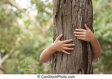 Loving nature - kid hands embracing a tree trunk