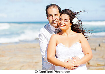 loving newlywed couple on beach