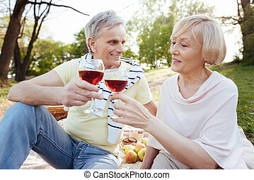 Loving old couple enjoying wine in the park - Sharing...