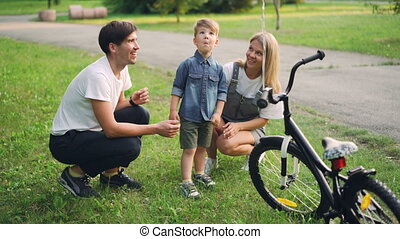 Loving parents are making surprise for little son closing his eyes and giving him new bicycle as present, happy boy is looking at bike and talking to mother and father.