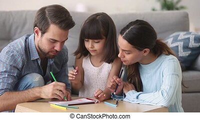 Loving parents drawing with little daughter at home - Family...