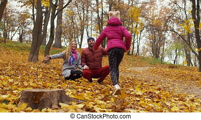 Loving parents embracing little daughter in autumn -...