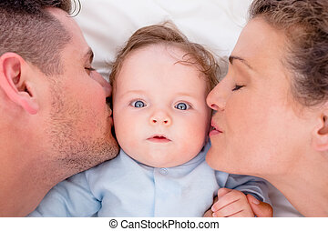 Loving parents kissing baby - High angle of loving parents ...