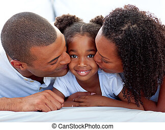 Loving parents kissing their daughter lying on a bed