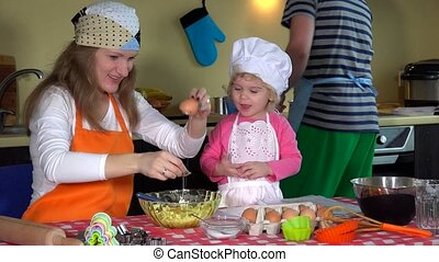 Loving parents with cute toddler girl with chef hat...