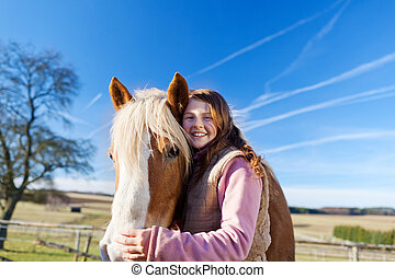 Loving portrait of a girl and her horse outdoors on a bright...