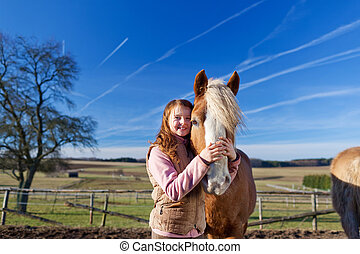 Loving portrait of a happy girl and her horse outdoors on a...