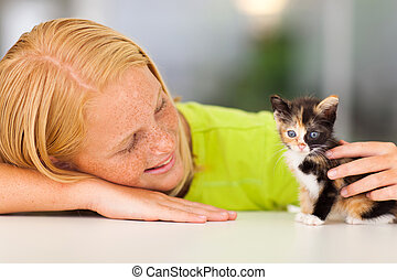 loving pre teen girl playing with kitten
