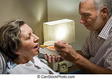 Loving retired husband feeding his ill wife