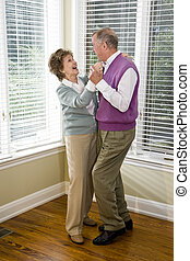 Loving senior couple dancing in living room