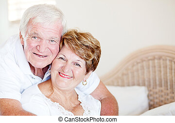 loving senior couple hugging in bedroom