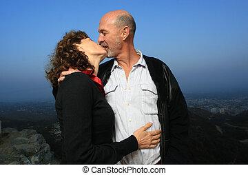 Loving senior couple kissing outdoors