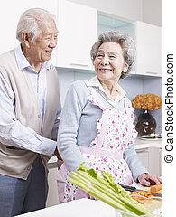 loving senior couple - senior man tying apron for his wife.