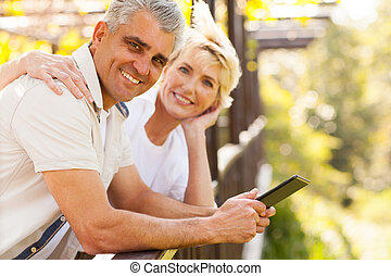 senior couple with tablet computer outdoors