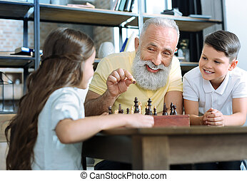 Loving senior gentleman smiling while teaching grandchildren chess