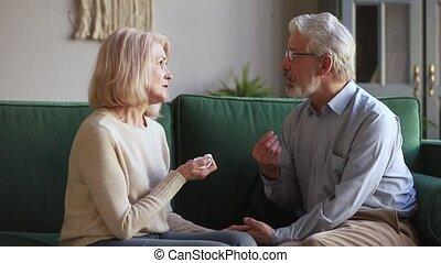 Loving senior husband holding hand of sad wife giving support