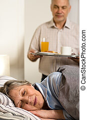 Loving senior husband serving breakfast to wife