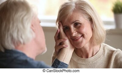 Loving senior husband stroking face of aged wife confessing...
