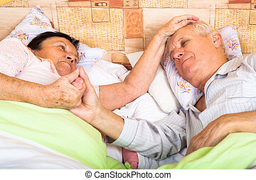 Close up of loving senior couple relaxing in bed.