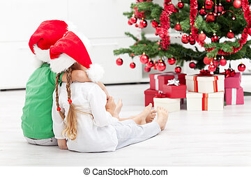Loving siblings in front of the christmas tree
