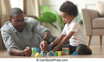 Loving single black father helping little kid son playing...