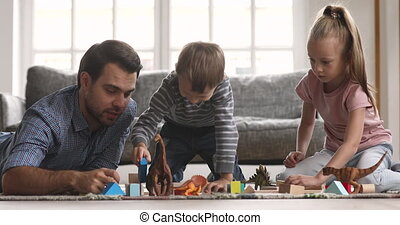 Loving single father lying on floor with adorable little son and daughter, playing with toys together in living room. Happy young daddy enjoying free weekend leisure playtime with children siblings.