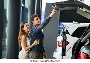 Loving smart couple choosing a car at the car dealership showroom