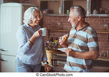 Loving smiling aged couple having breakfast in the kitchen