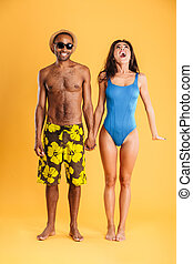 Loving smiling couple in swimwear holding hands