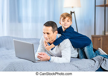 Loving son back-hugging his father working on laptop