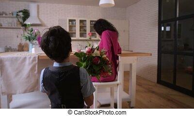 Loving son congratulating mom with flowers - Joyful,...