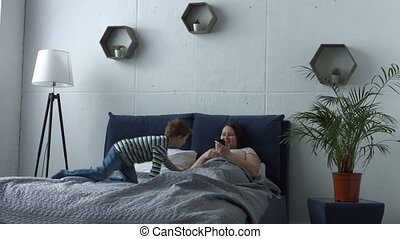 Loving son embracing his mother in bed after awake