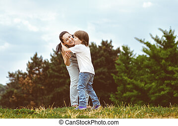 Loving son kissing his happy mother on the cheek. Toned...
