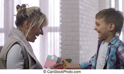 Loving son presenting gift box to surprised mother - Smiling...
