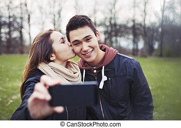 Loving teenage couple taking self portrait - Pretty young...