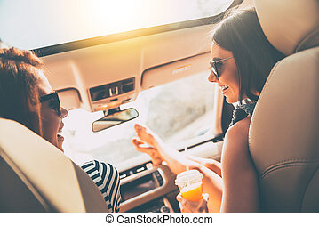Loving this road trip. Rear view of two beautiful young cheerful women looking at each other with smile while sitting in car