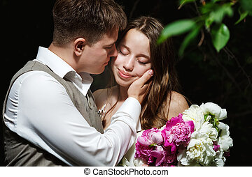 Loving wedding couple kissing in the park