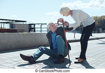 Loving wife helping elderly husband to stand up