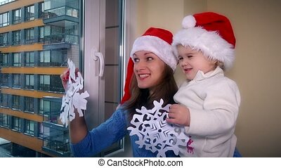Loving woman and child girl with red santa hats glue paper snowflakes on window