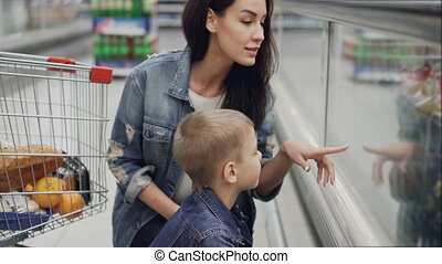 Loving woman is choosing ice-cream in freezer for her cute little son looking at food through glass pointing at items and talking. Happy family and buying food concept.