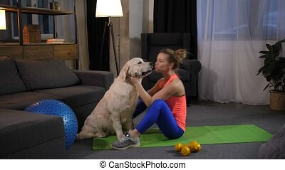 Loving woman owner kissing dog doing abs exercises -...