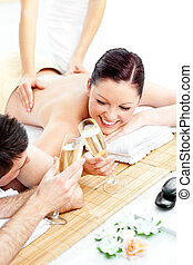 Loving young couple drinking champagne lying on a massage table