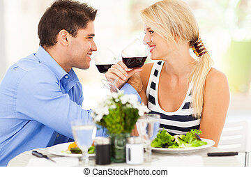 loving young couple drinking wine in restaurant