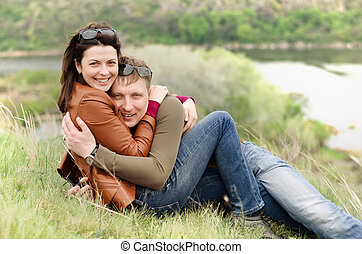 Loving young couple embracing on a hill top