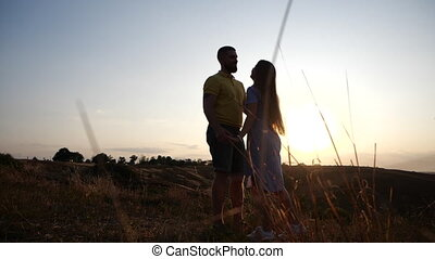 Loving young couple girl and guy hold hands, flirt kiss and hug on the field against the background of dawn in slow motion. Happy and romantic relationship. Date on the field at sunset background.