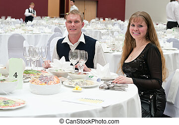 Loving young couple in restaurant at round white table....