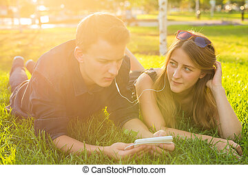 Loving young couple in summer park listening music.