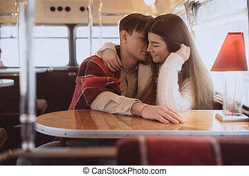 Loving young couple in winter time sitting in a cafe